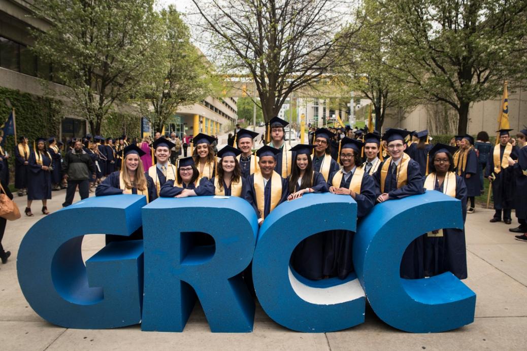 "Thirteen graduates stand behind giant letters that say ""GRCC"" on the Student Plaza."