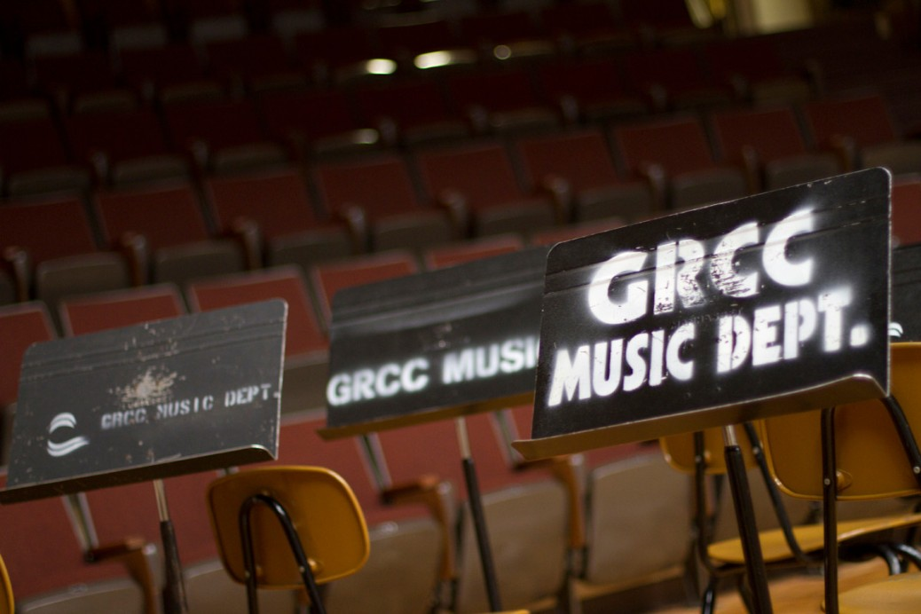 "Music stands in an auditorium are labeled: ""GRCC Music Dept."""