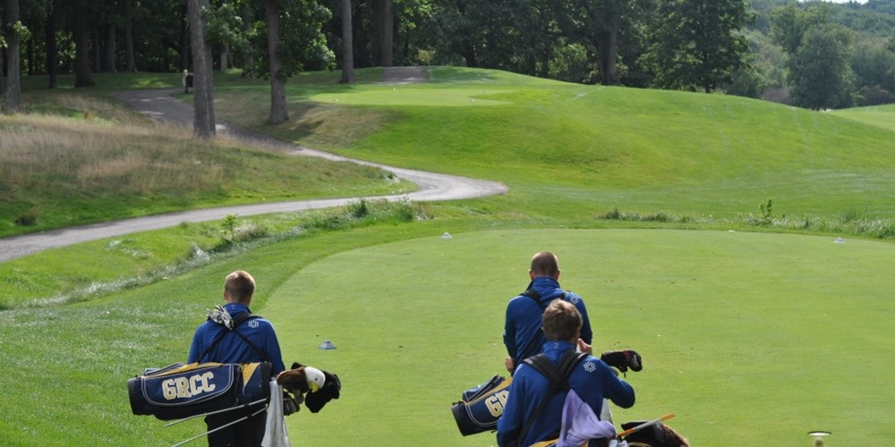 Three members of GRCC's golf team carry their bag as they walk onto the green.