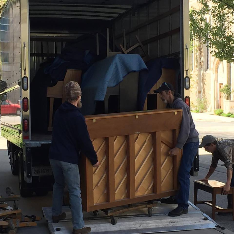 Two men stand on a truck lift with an upright piano. Another man carries a piano bench. Three other pianos are in the back of the truck.