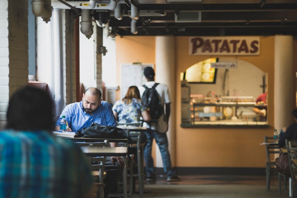 Some students are eating and studying at tables in Winchester Alley, while another student reads the menu posted at Patatas.