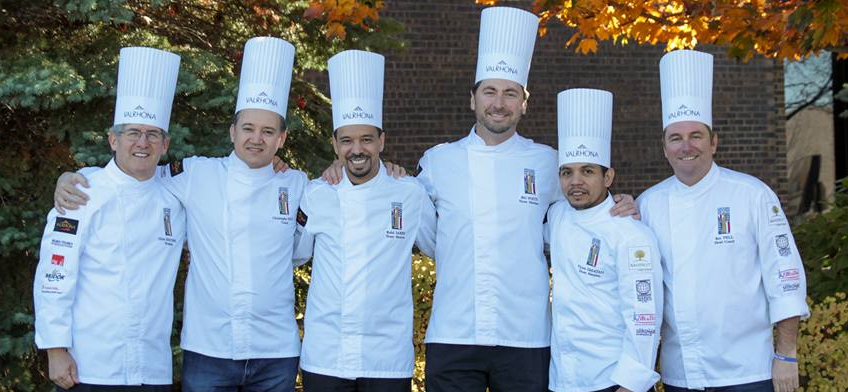 Six chefs -- Gilles Renusson, Christophe Feyt, Rabii Saber, Bill Foltz, Victor Dagatan and Roy Pell -- stand near trees.