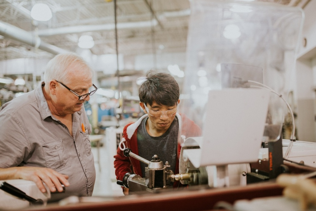 Machinist/CNC assistant professor Steve Henkelman works with student SawTe Naing on an engine lathe using a form tool to make a ballpeen hammer head.