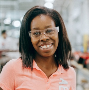 Jerrittea Roseburgh, wearing safety goggles, stands in a machinist lab.