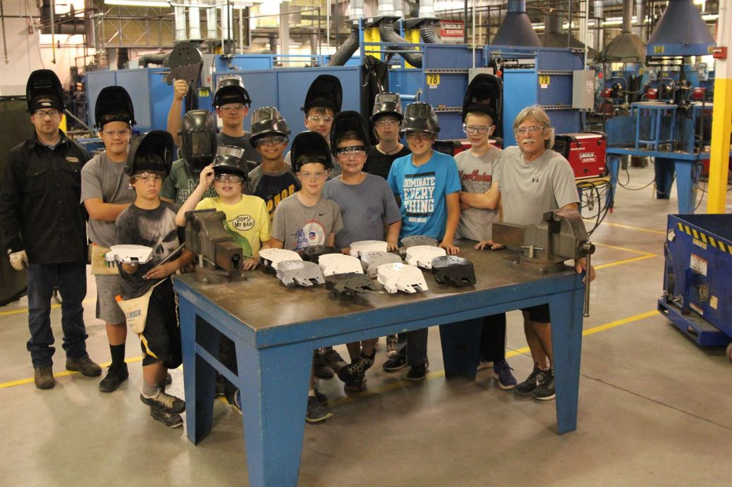 Kids in the Manufacturing Camp, wearing welding helmets, stand with their instructors behind a table at Tassell M-TEC. Their models of the Millenium Falcon sit on the table.