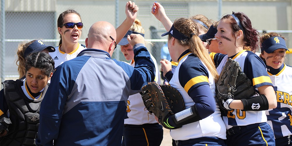 The coach and GRCC softball players raise their hands as they stand in a circle on the field.