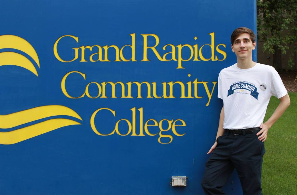Cale Merdzinski stands by the Grand Rapids Community College sign.
