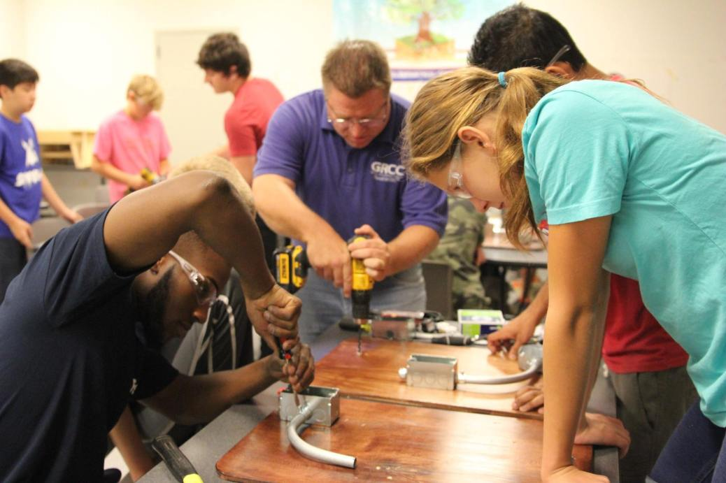 A Construction Electrician program student screws an electrical box to a piece of plywood as campers watch. An instructor drills a hole into another piece of plywood.