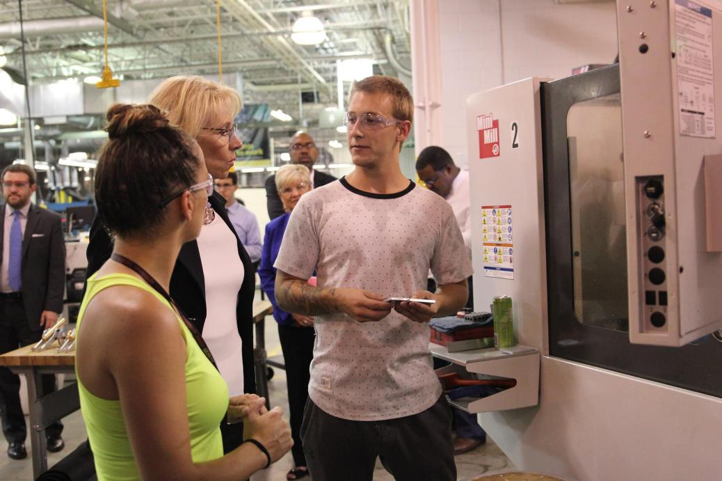 Two students, standing by a machine at Tassell M-TEC, talk to Betsy DeVos.