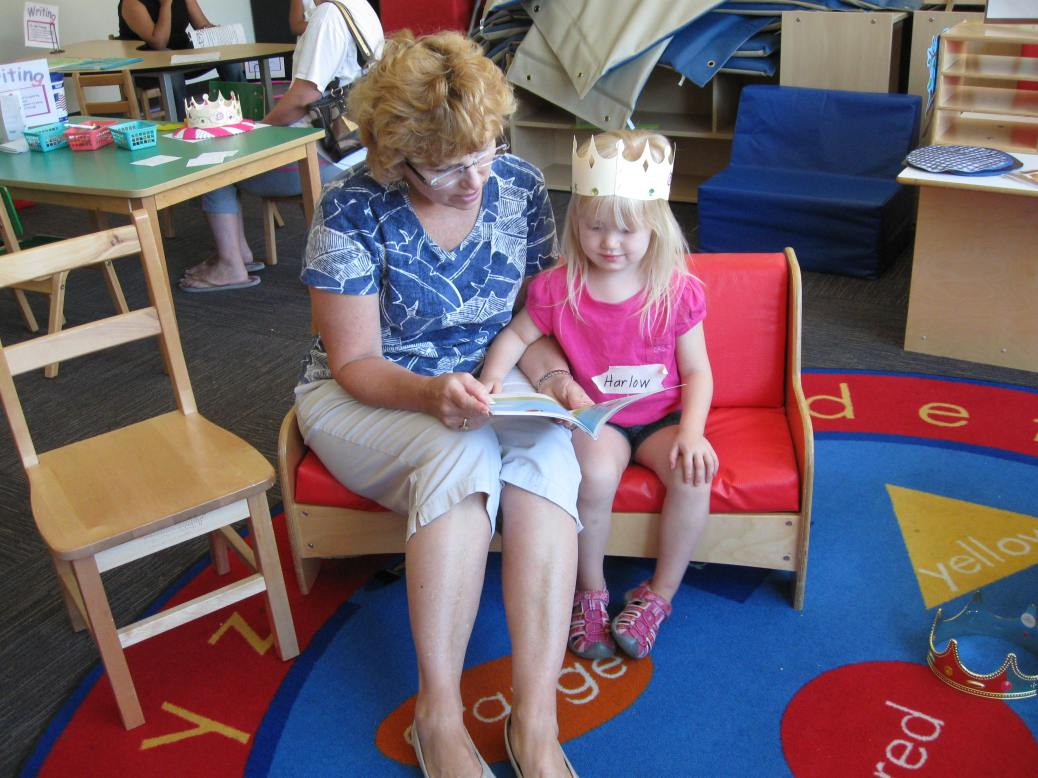 A woman reads to a little girl wearing a paper crown.