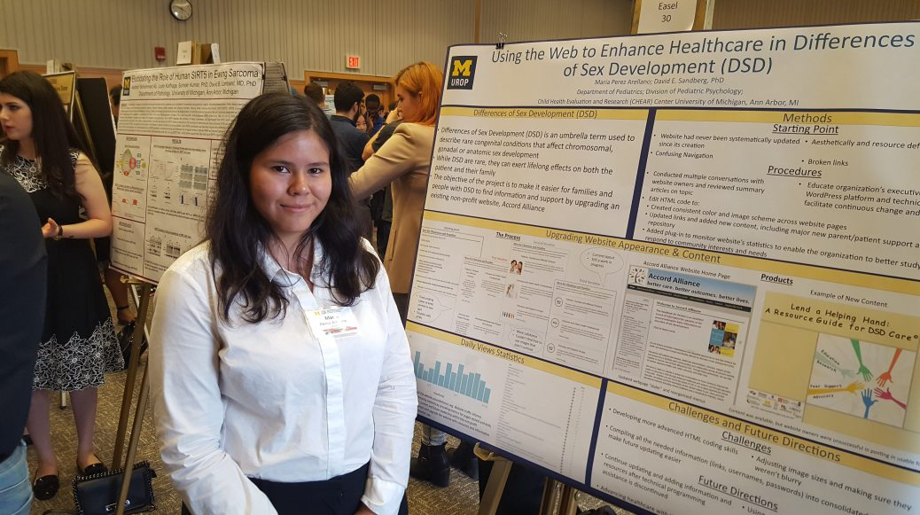 "Maria Perez stands next to her poster on ""Using the Web to Enhance Healthcare Differences o Sex Development."""