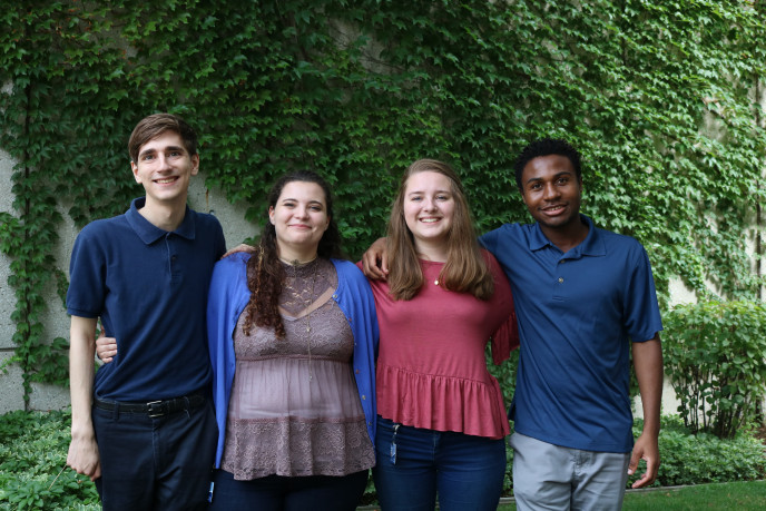 Cale Merdzinski, Tatum Kovach, Kaitlynn Karl and Kyezie Bwanangela stand next to each other in front of an ivy-covered wall.