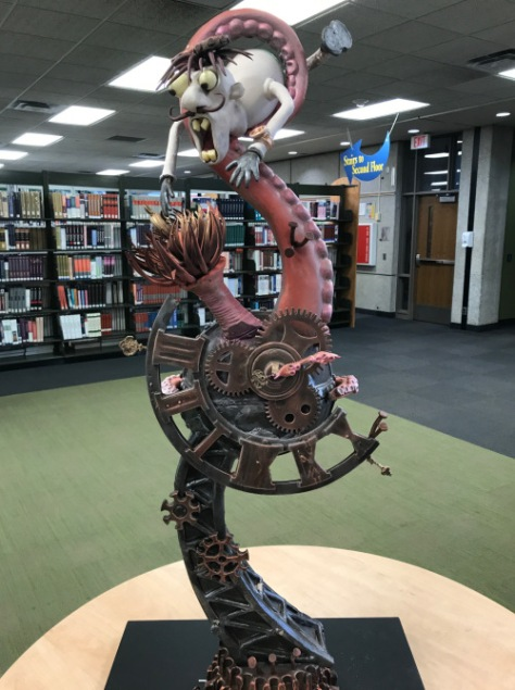 A chocolate sculpture that depicts a man wrapped in a tentacle atop clock works sits in the library.
