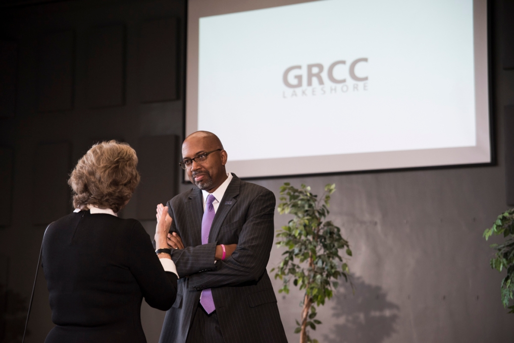 """President Pink listens to a woman. They are standing near a video screen that says """"GRCC Lakeshore."""""""