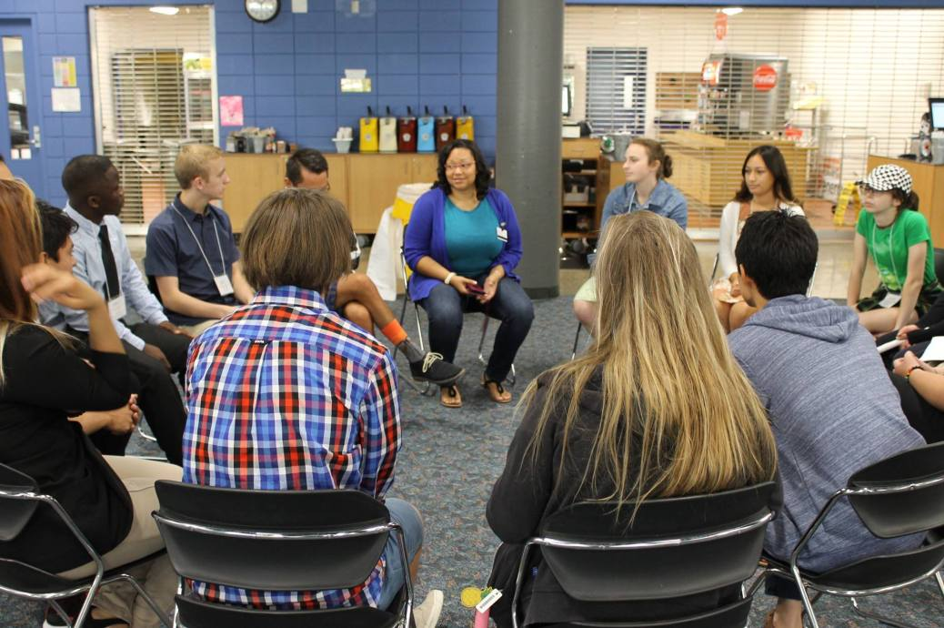 A woman talks to students seated in a circle in the Raider Grille.