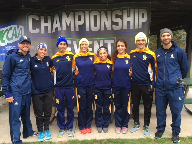 """Five cross country runners and three coaches stand in front of a banner that says """"Championship Event."""""""