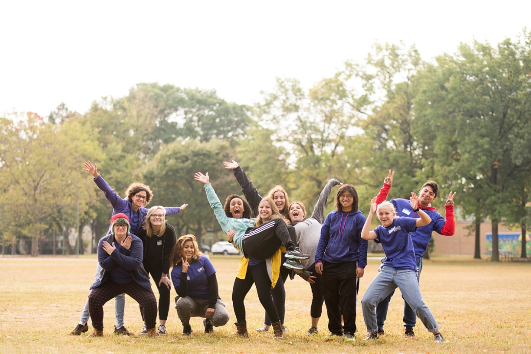 Eleven students make goofy poses in a park.