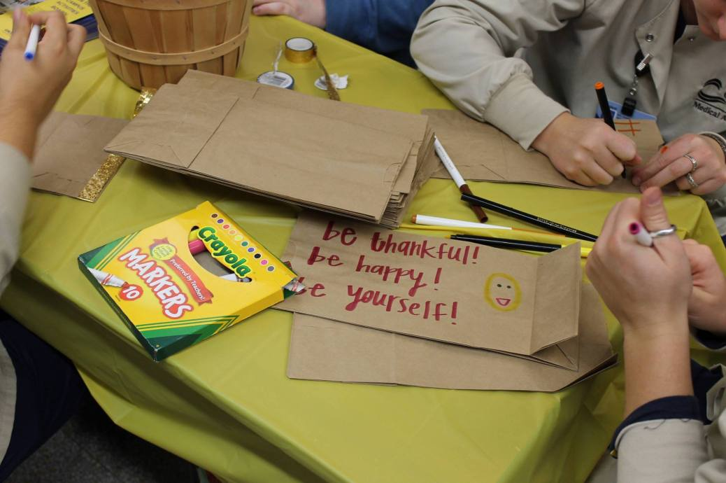 "A student writes: ""Be thankful! Be happy! Be yourself"" on a lunchbag."