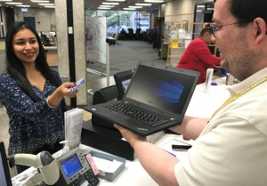A student uses her RaiderCard to check out a laptop from the library circulation desk.