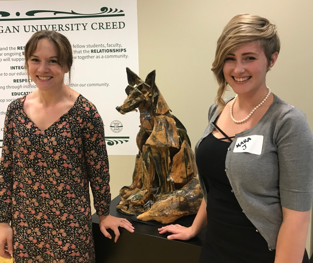 Alyson Mabie and Kara Jueckstock stand next to a wolf statue in a hallway at Eastern Michigan University.