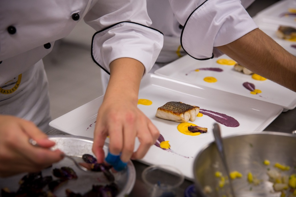 Two culinary students work to plate Nations' Cup entries.