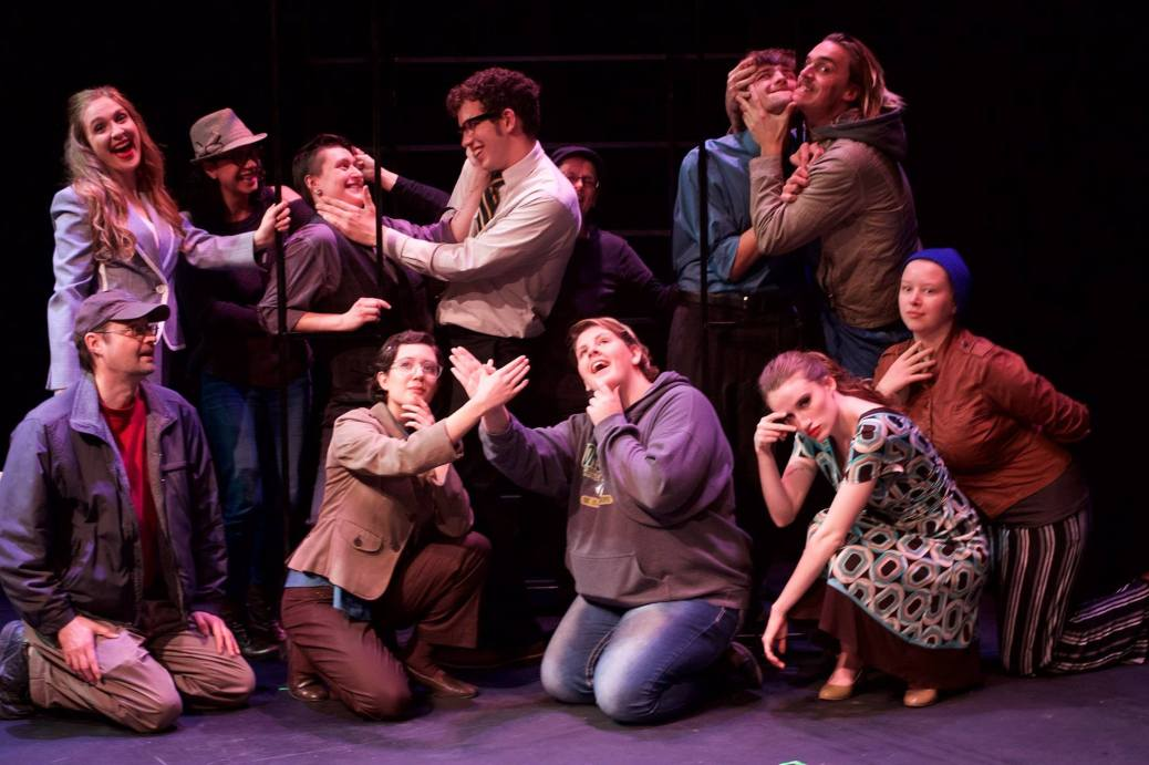 Twelve student-actors, five kneeling in front, make faces.