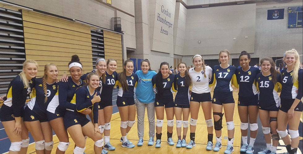 The volleyball team stands in a row in the fieldhouse.