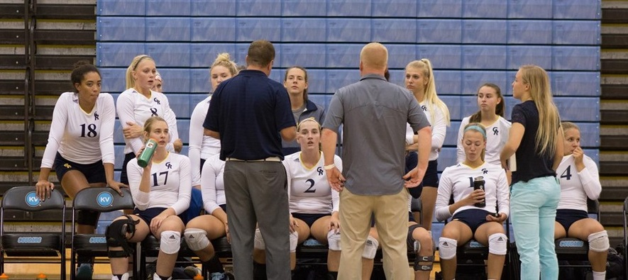 Volleyball team members sit on the sidelines, listening to the coaches.