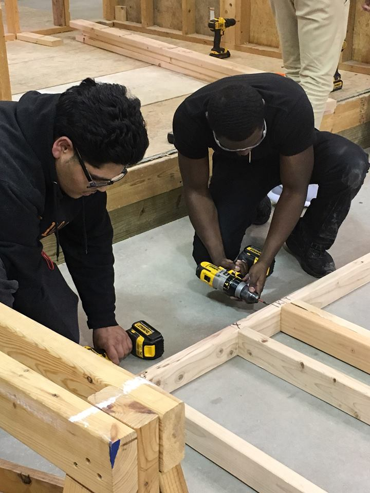 Two students use a drill on a frame.