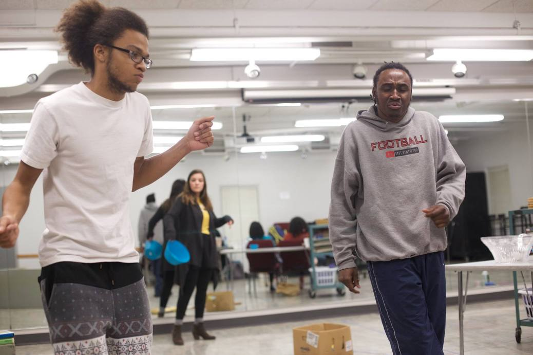 Two student actors dance during rehearsal.