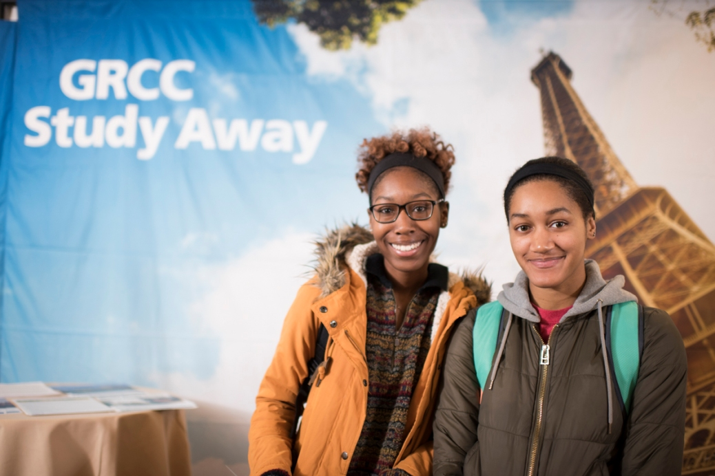 Two students stand in front of a GRCC Study Away banner.