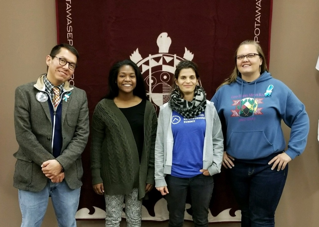 Drewyn Talley, Destiny Steffens, Lesley Bos and Myriah Williams stand in front of a banner representing the Nattowaseppi Heron Band of Potawatomi Indians.