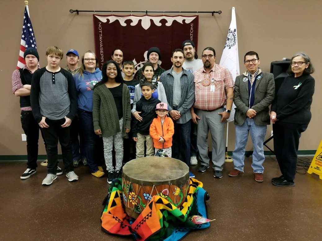 Native American Student Organization members and families stand behind a large drum.