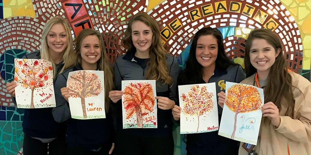 Hannah Stearns, Lauren Helsen, Lena Thompson, Hailey DeKorte and Payton Helsen hold up pictures of trees they've made.