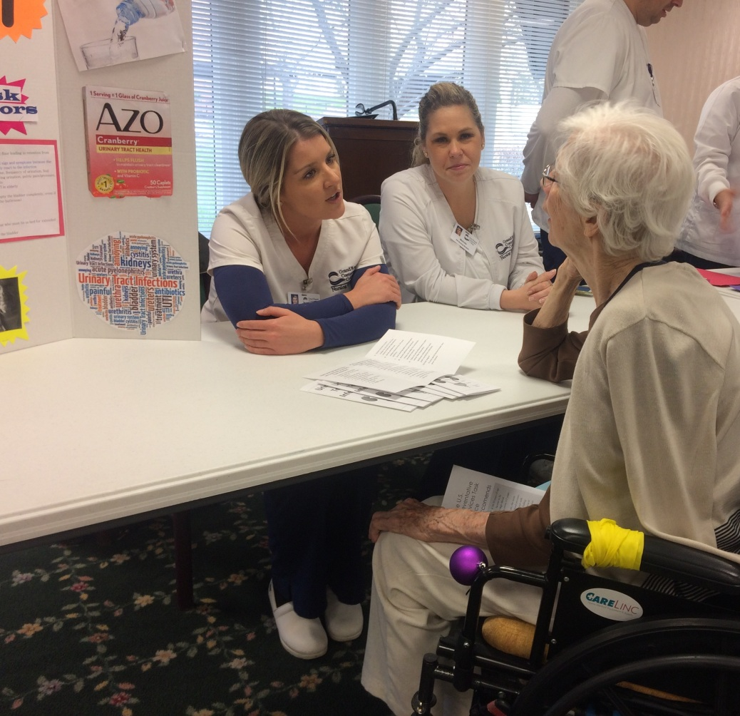 Two nursing students, seated behind a table, talk to a woman in a wheelchair.