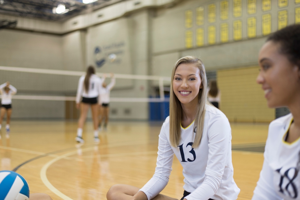 Kendra DeJonge sits on the volleyball court; other team members are practicing behind her.