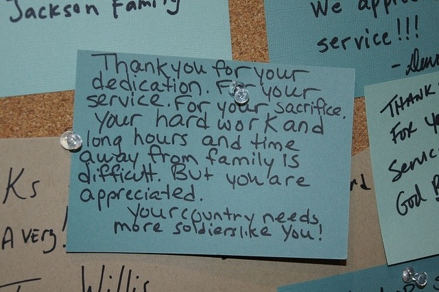 A letter to a military service person, pinned to a bulletin board, reads: Thank you for your dedication. For your service. For your sacrifice. Your hard work and long hours and time away from family is difficult. But you are appreciated. Your country needs more soldiers like you!
