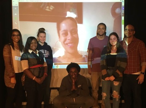 Student actors and Sammy A. Publes stand in front of a video screen showing Dominique Morisseau.