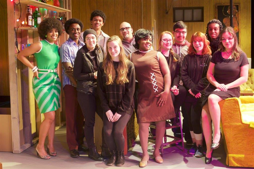 "The cast of ""Detroit '67"" dressed in 1960s fashions, stand on the set of a basement bar."