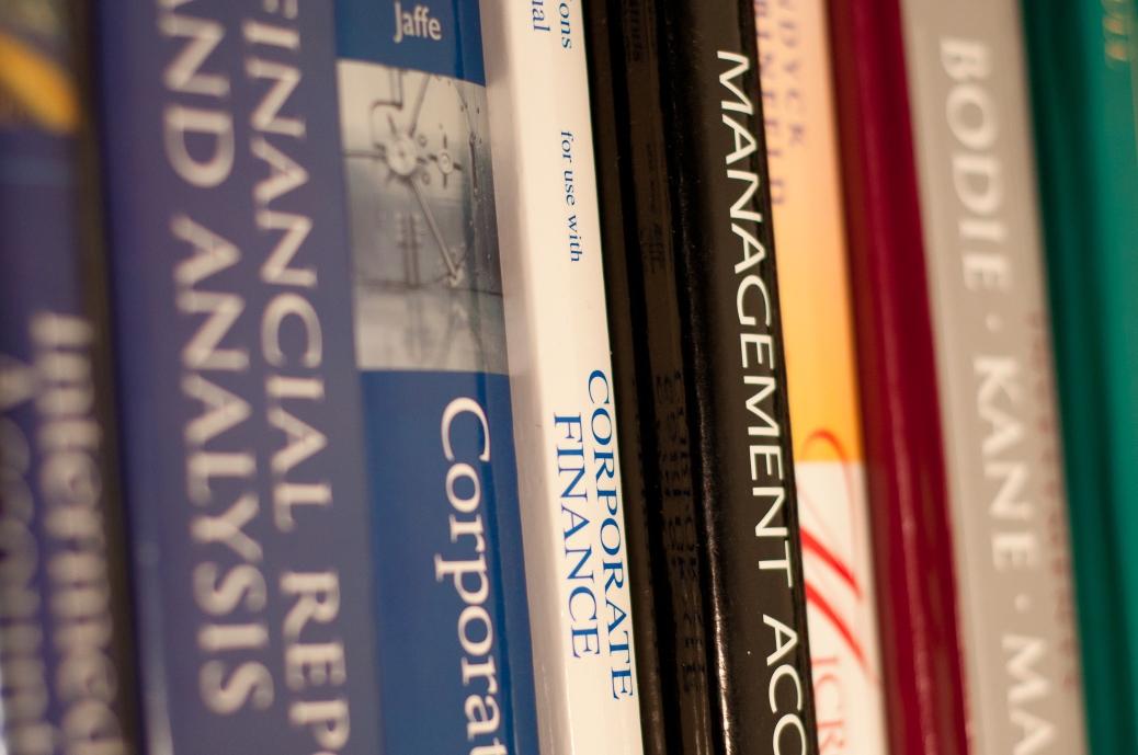 Business textbooks line a shelf.