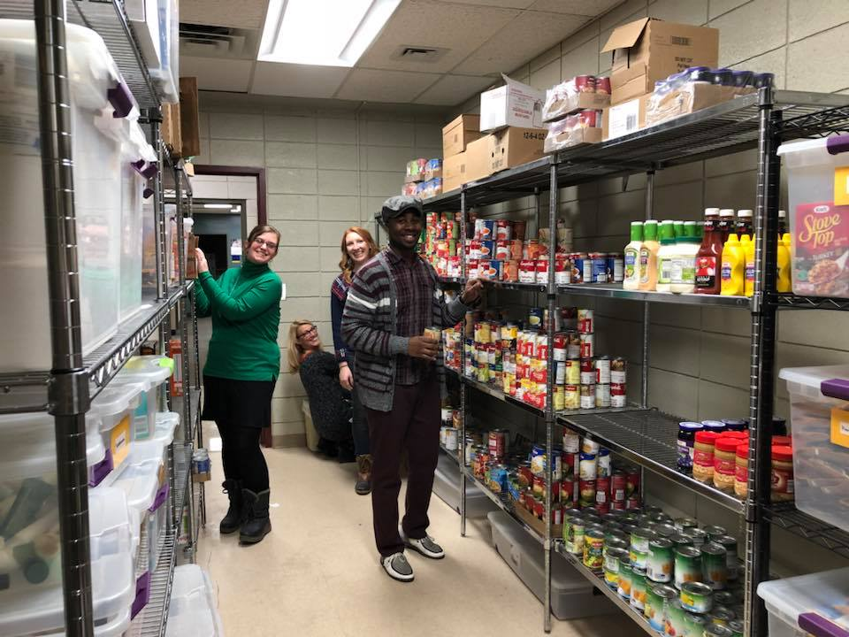 Four students put donations on the shelves of the Student Food Pantry.