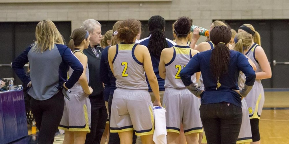 The women's basketball team stands in a huddle.