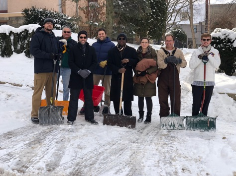 Eight members of the IT Department stand with shovels on a freshly cleared Fountain Street sidewalk.