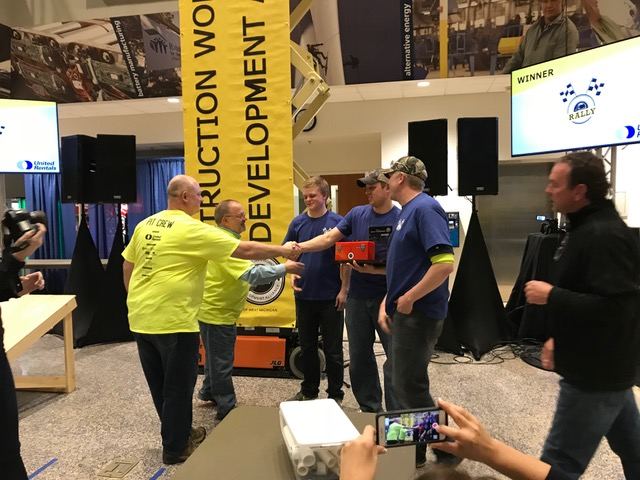 Two men shake hands with the winning Dan Vos Construction team.
