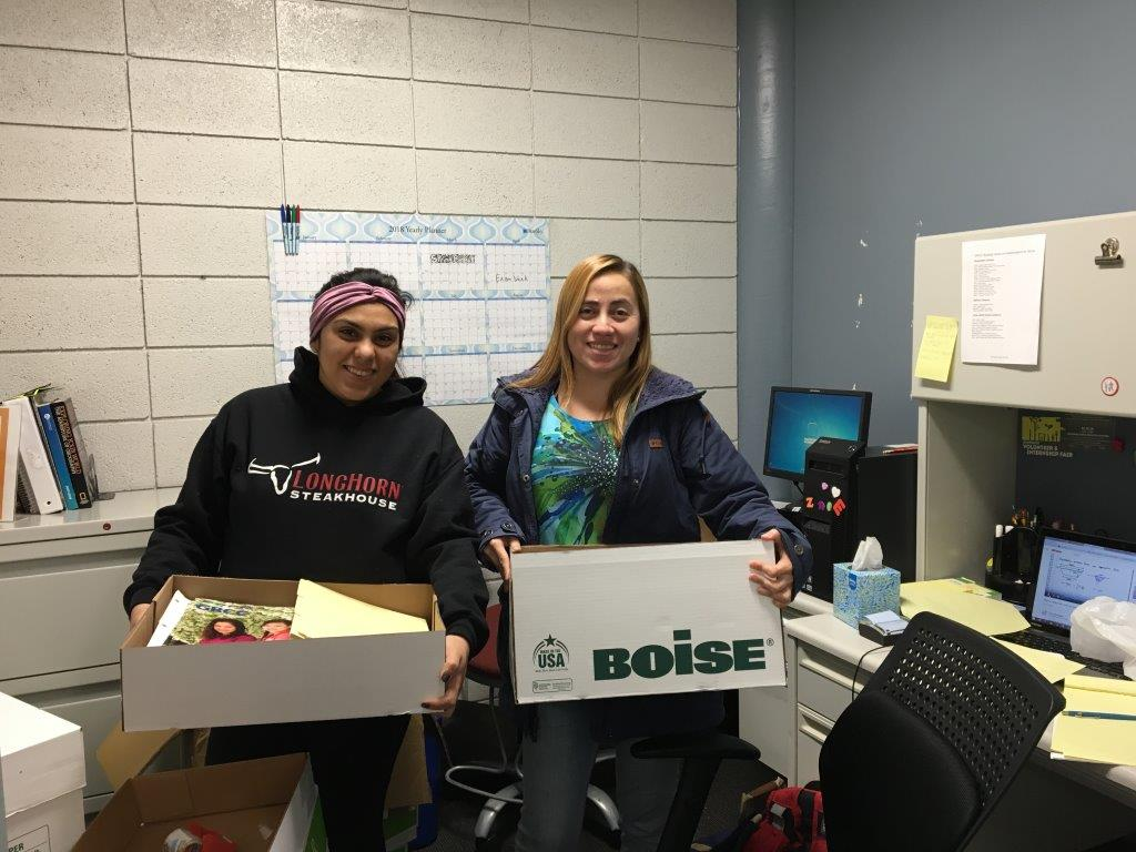 Two students hold boxes of supplies for Puerto Rico.