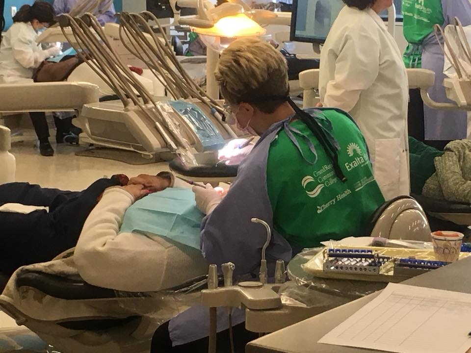 A dental student cleans the teeth of an elderly patient.