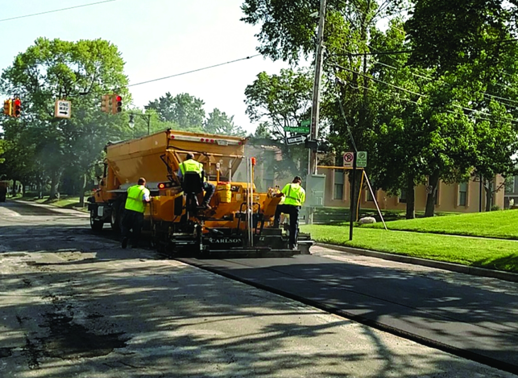 Three people work with equipment to pave a street.