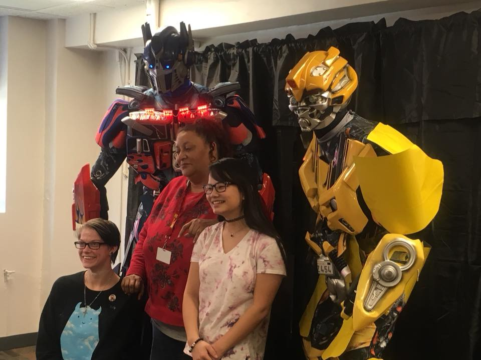 Three student employees pose with two people in Transformers costumes.