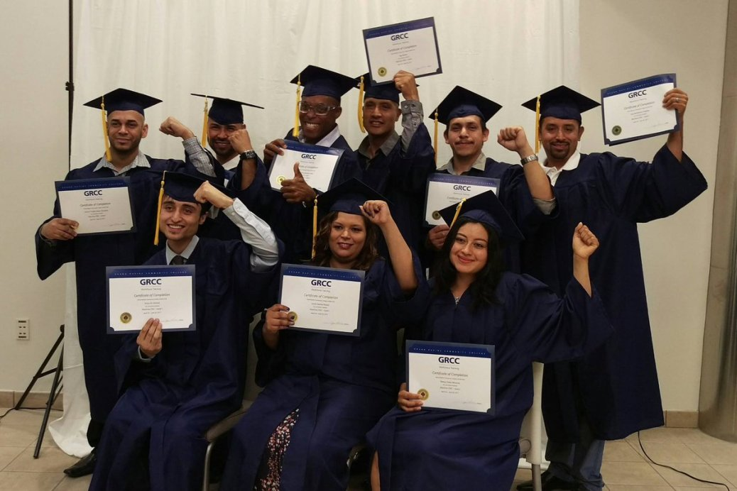 Ten students in caps and gowns show off their certificates.