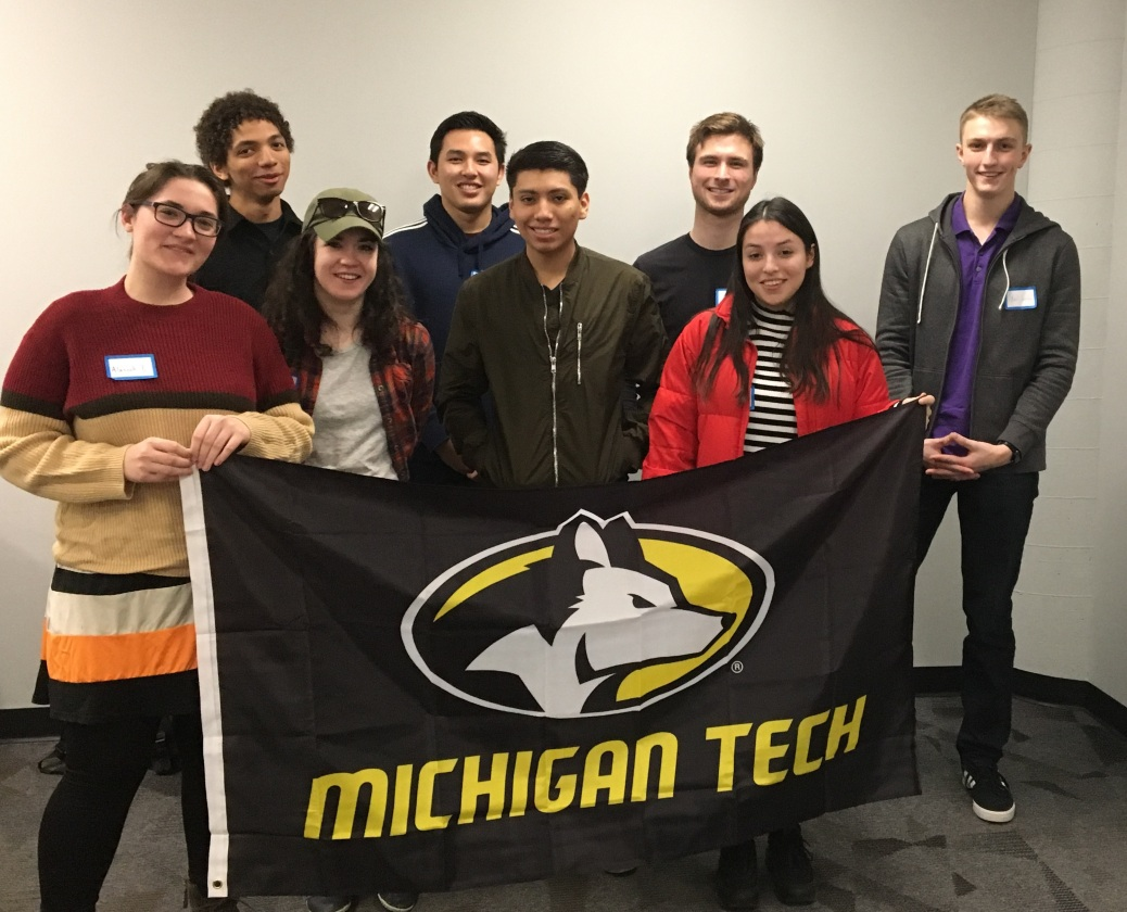 Eight TRIO students hold up a Michigan Technological University flag.